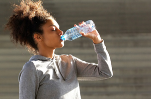 woman_stands_outside_in_sun_with_eyes_closed_drinking_water